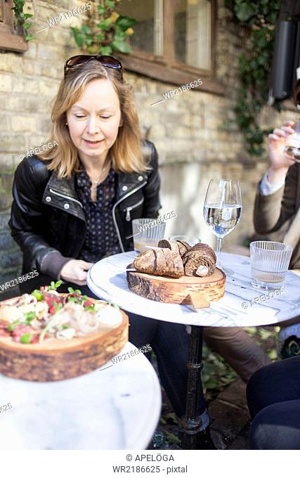 Mature woman looking at cold cuts in plate at outdoor restaurant