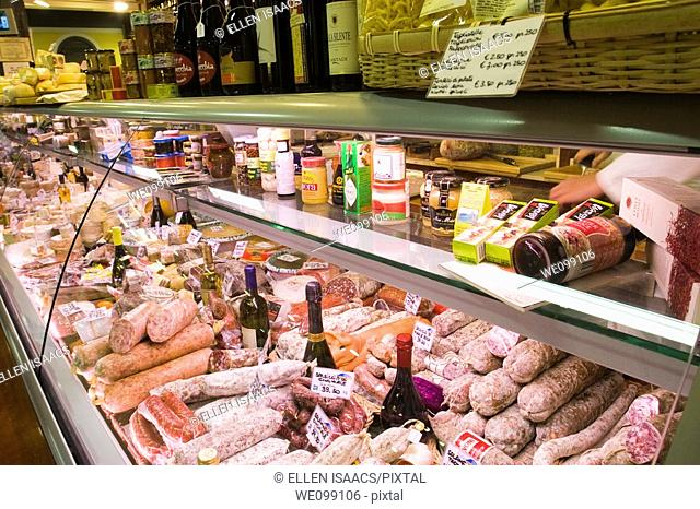 Sausages, cheeses, and other lunch makings in a deli display case at San Lorenzo market in Florence, Italy