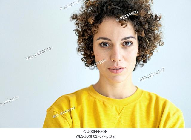 Portrait of confident woman wearing yellow sweater