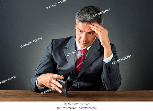 Shocked businessman with empty wallet sitting at desk against gray background