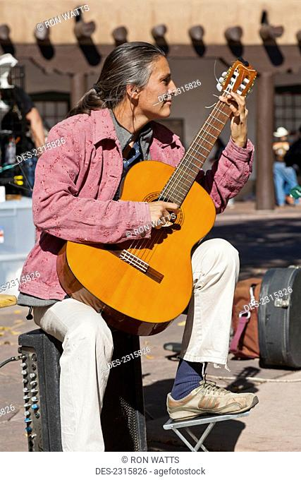 Usa, New Mexico, Guitarist Performing For Tourists In Historic Plaza In Downtown; Santa Fe