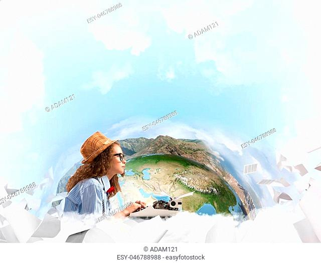 Portrait of thoughtful woman writer looking away and using typing machine while sitting at the table with flying papers and Earth globe among cloudy skyscape on...