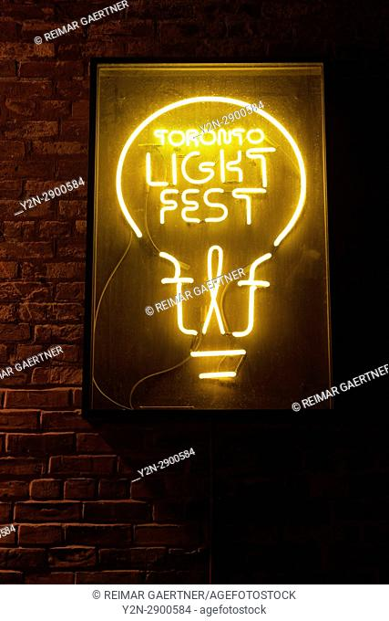 Neon sign logo for the Toronto Light Festival on a brick wall at night in the Distillery District