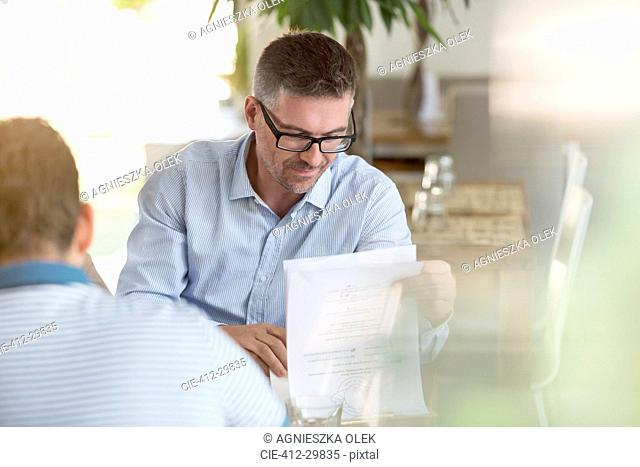Businessman reviewing notes in cafe