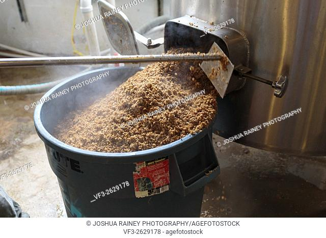 EUGENE, OR - NOVEMBER 4, 2015: Used mash is emptied from the mashing machine into a large bucket for recycling at the startup craft brewery Mancave Brewing