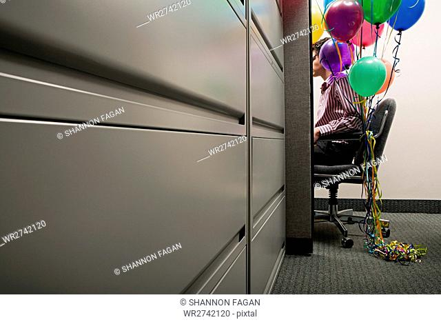 Businessman sat with balloons tied to his chair