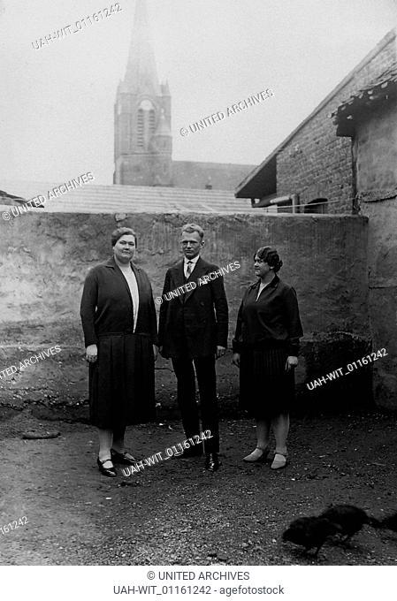 ZWei Frauen und ein Mann lassen sich im Hühnerhof eines Hauses in Stommeln fotografieren. Im Hintergrund ragt die Pfarrkirche St. Martinus auf