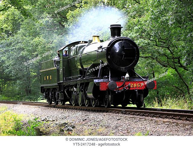 A GWR heavy freight 2-8-0 steam locomotive heads throught Eyemore woods at Trimpley on the Severn Valley Railway, Worcestershire, England, Europe