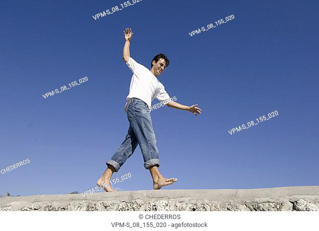 Low angle view of a young man walking on the wall
