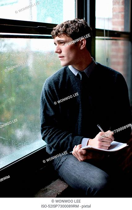 Businessman writing in windowsill