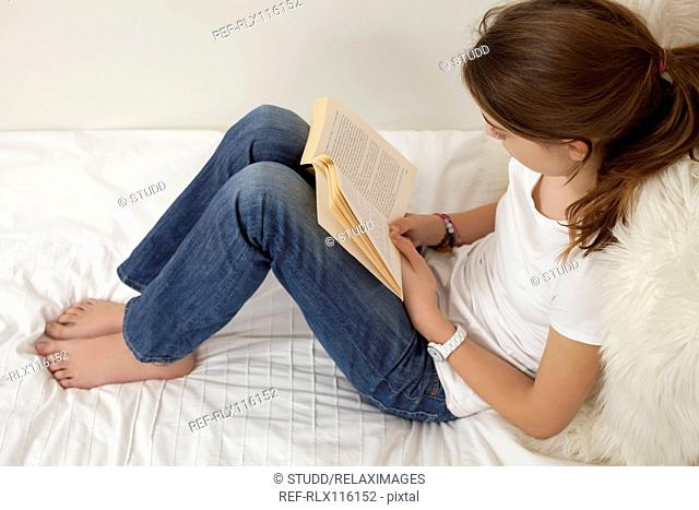 Girl sitting on bed reading book