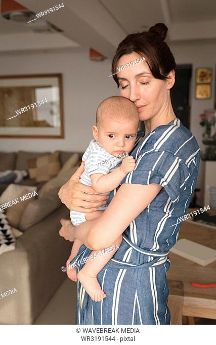 Mom with closed eyes holding her baby in living room