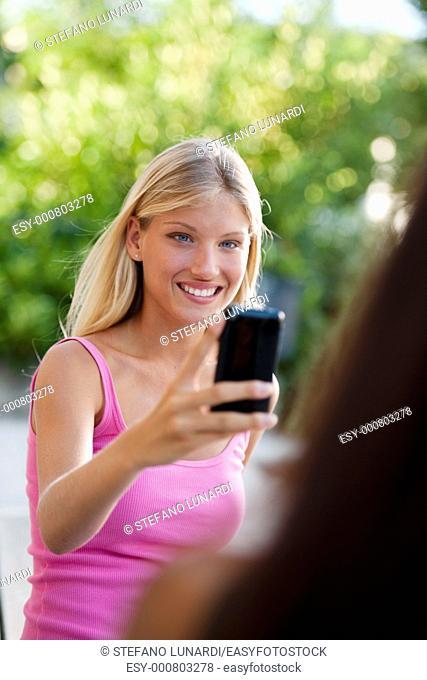 Beautiful teenage girls photographing with camera phone