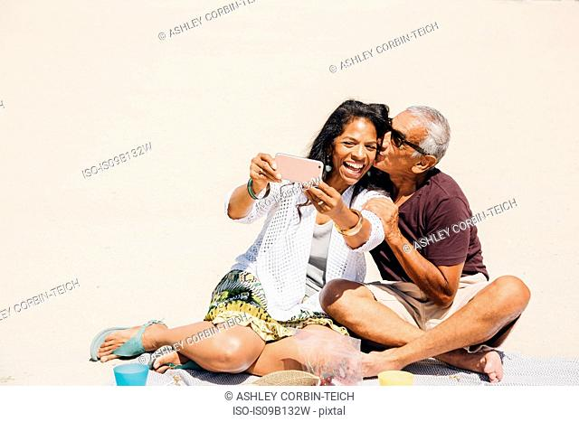 Senior couple sitting on beach, taking selfie with smartphone, Long Beach, California, USA