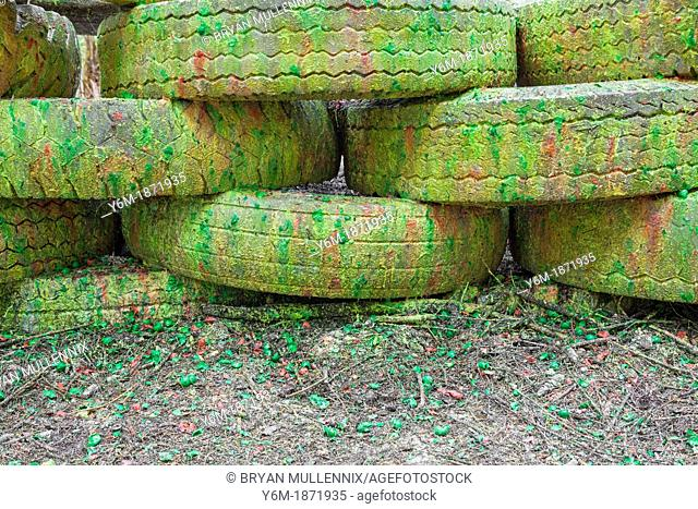 Paint covered barricade made of tires on paintball field, Oregon