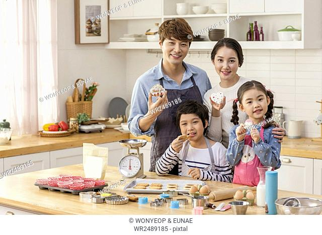 Harmonious family eating cookies together in kitchen