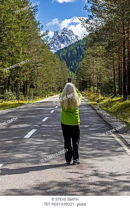 Woman taking selfie on highway by Tre Cime di Lavaredo, Italy