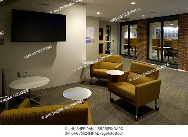 A photo of rolling chairs with tables and a flat screen television at Brody Learning Commons, a study area, at Johns Hopkins University, Baltimore, Maryland