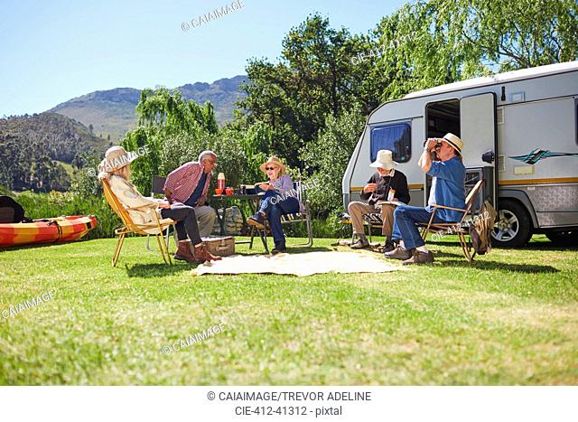 Active senior friends relaxing outside camper van at sunny summer campsite