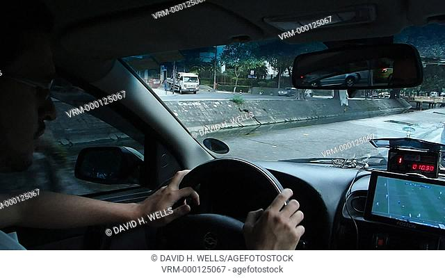 Young man watching football while driving taxi-cab, Rio De Janerio, Brazil