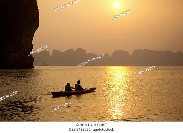 Silhouette of couple in kayak at sunset Bai Tu Long Bay in Halong Bay; Vietnam