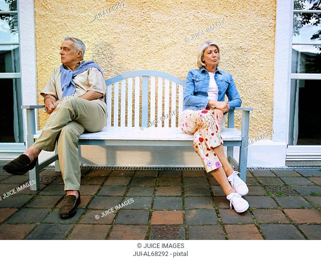 Mature couple sitting apart on a bench