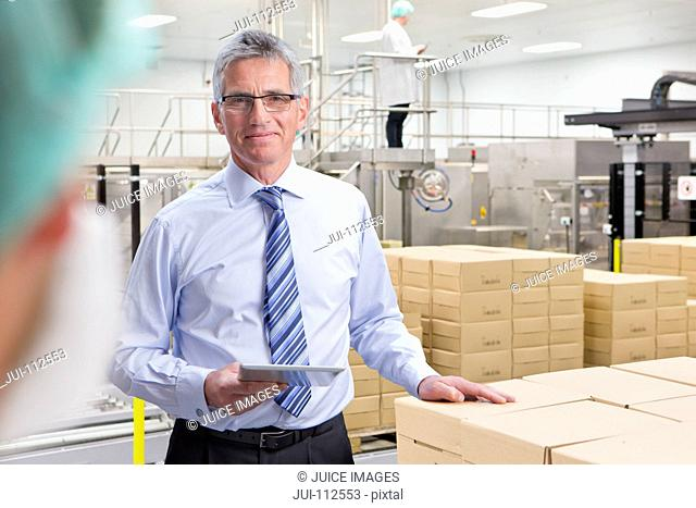 Portrait of smiling businessman with laptop at food packaging production line