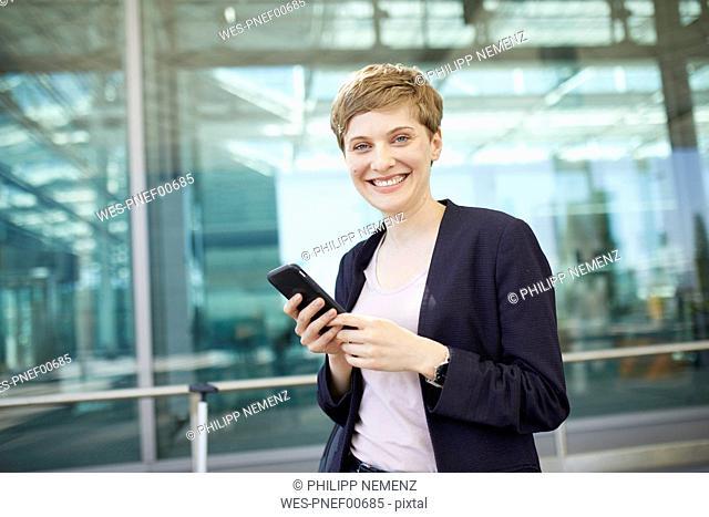 Portrait of blond businesswoman using smartphone