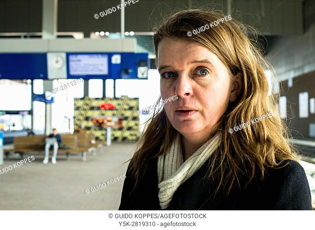Breda, Netherlands. Mid adult caucasian woman waiting at the Railway Station's Platform 3 for her connecting train eastbound