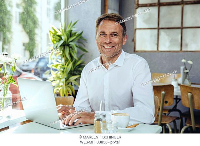 Portrait of smiling businessman working in cafe with laptop