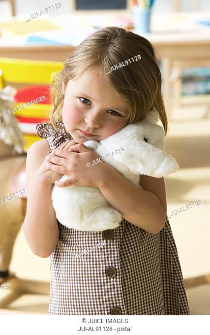 Preschool girl hugging stuffed animal