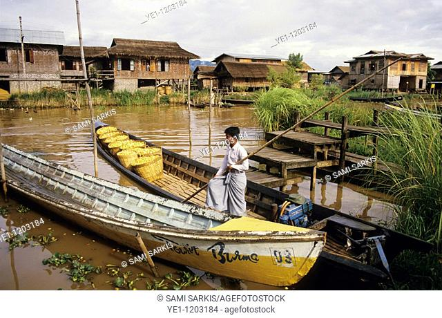 Man waiting to disembark from a boat full of tomatoes on Inle Lake, Nyaung Shwe, Burma