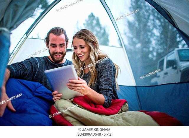 Young couple reading digital tablet in tent, Lake Tahoe, Nevada, USA