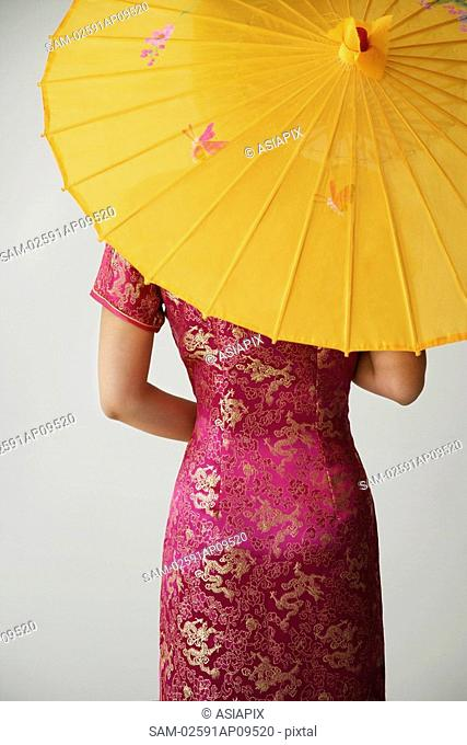 young Chinese woman in pink cheongsam holding yellow umbrella