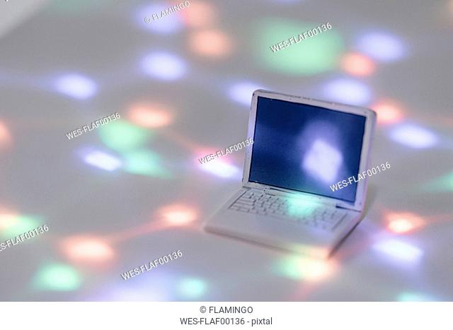 Miniature laptop model surrounded by points of light
