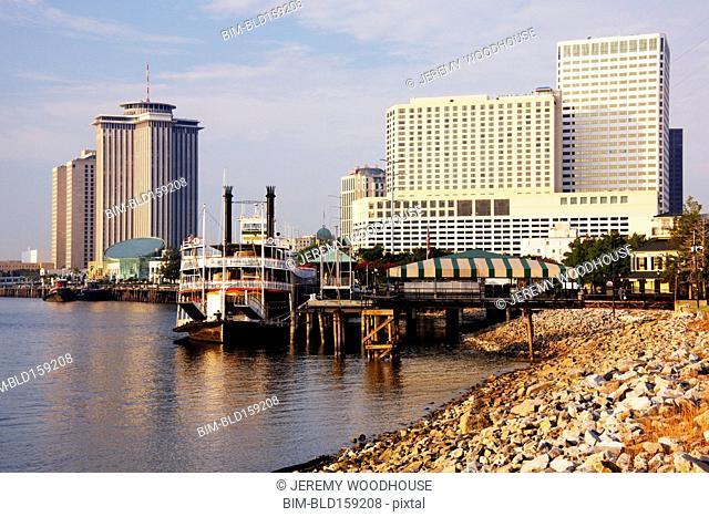 Riverboat and highrise buildings in urban waterfront, New Orleans, Louisiana, United States