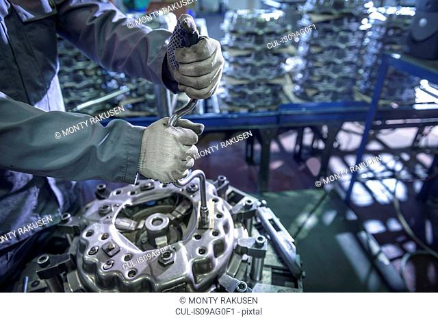 Close up of engineer assembling industrial clutch on production line