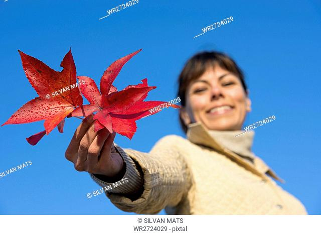 Happy woman holding red leaf