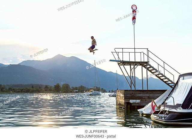 Austria, Sankt Wolfgang, man jumping from platform into lake
