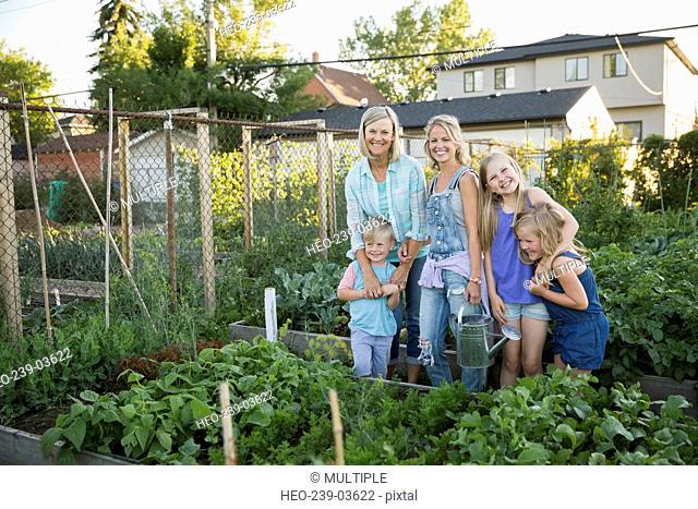 Portrait multi-generation family tending to vegetable garden