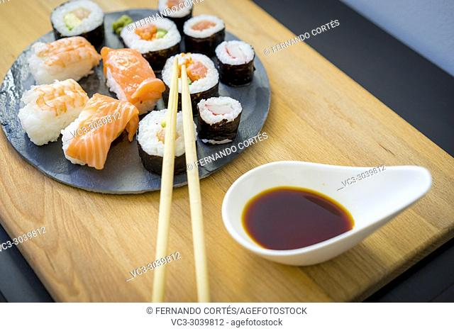 Maki on a wooden table on black slate plate with soy sauce and chopsticks