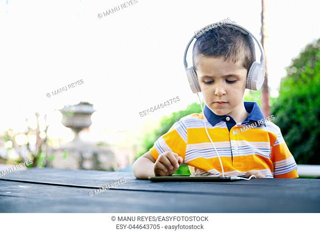 boy listening to music with withe headphones on the outside. Madrid, Spain