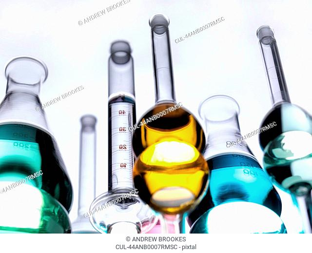 Beakers with liquids on reflective table