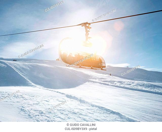 Sunlit ski lift in snow covered mountain landscape, Alpe Ciamporino, Piemonte, Italy