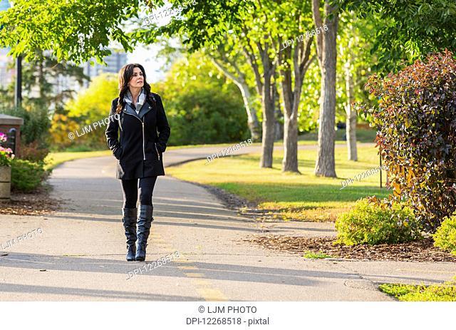 Mature businesswoman walking outdoors in a city park in autumn; Edmonton, Alberta, Canada