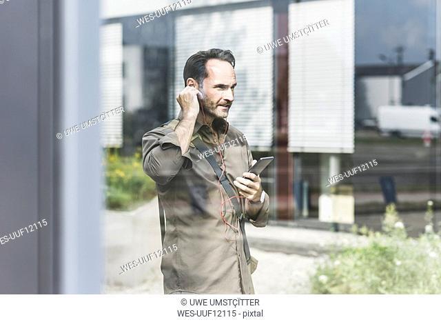 Businessman using smartphone and earphones