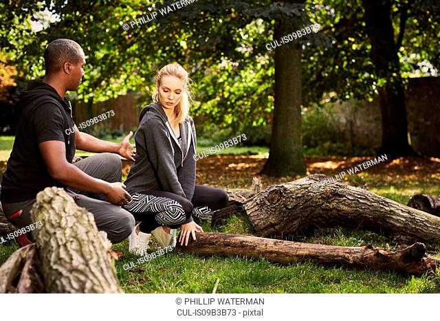 Personal trainer showing young woman how to lift tree trunk in park