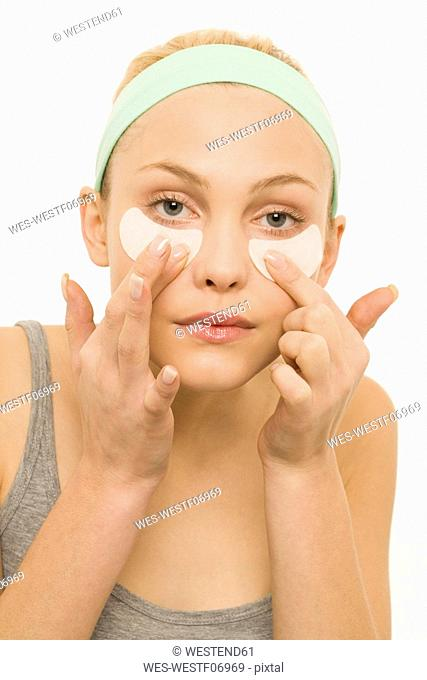 Woman applying adhesive plaster over nose, portrait