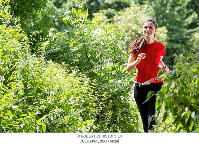 Woman jogging through forest