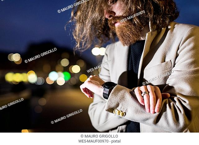 Stylish young man outdoors at night checking the time